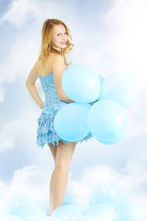 Girl with balloons on light background photo