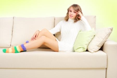 smiling girl sitting on sofa on light background Stock Photo - 16692253
