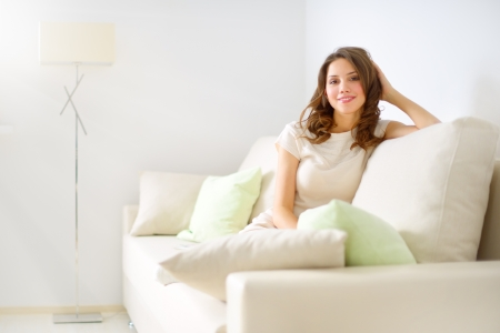 smiling girl sitting on sofa on light background photo