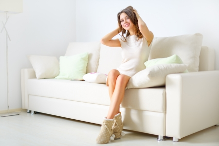 smiling girl sitting on sofa on light background Stock Photo - 16890551