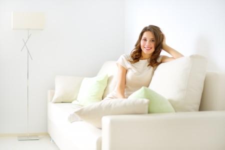 Ragazza sorridente seduta sul divano su sfondo chiaro Archivio Fotografico - 16792968