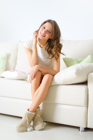 smiling girl sitting on sofa on light background