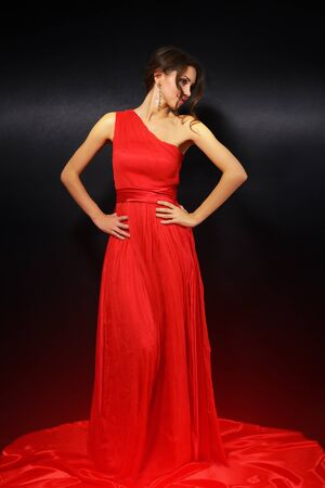 evening dress: elegant young woman in red dress on black background