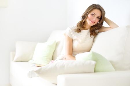 smiling girl sitting on sofa on light background Stock Photo - 17597221