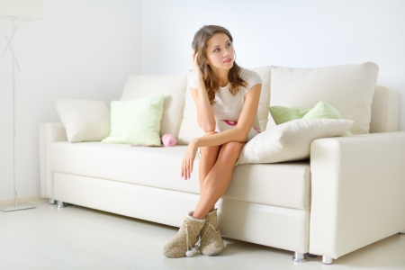 smiling girl sitting on sofa on light background Stock Photo - 17597207