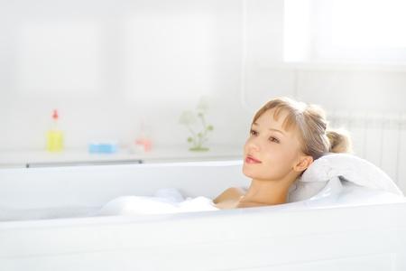 um jovem mulher só: Menina que relaxa na banheira no fundo claro