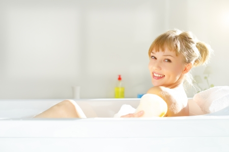 bathtub: girl relaxing in bathtub on light background Stock Photo