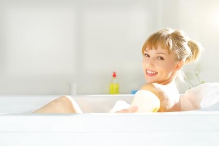 girl relaxing in bathtub on light background Foto de archivo