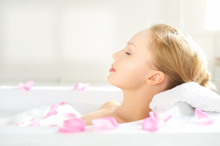 girl relaxing in bathtub on light background Stock Photo