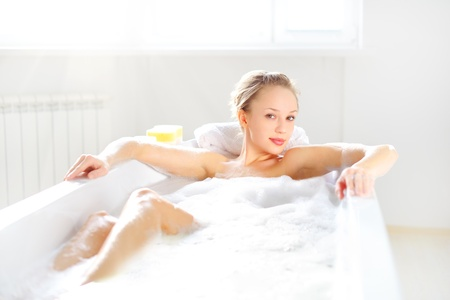 Attractive girl relaxing in bath on light background photo