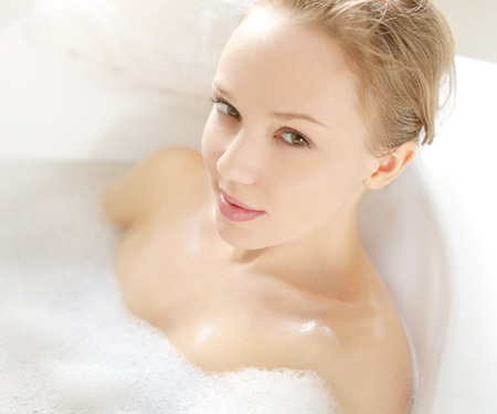women bathing: Attractive girl relaxing in bath on light background