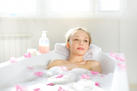 lying in bathtub: Attractive girl relaxing in bath on light background