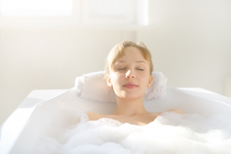 resting: An Attractive girl relaxing in bath on light background Stock Photo
