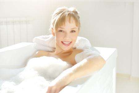 mujer ba�andose: Una muchacha atractiva se relaja en ba�o sobre fondo claro Foto de archivo