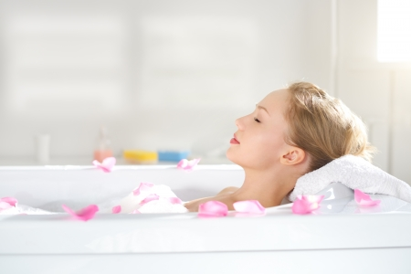 rest: An Attractive girl relaxing in bath on light background Stock Photo