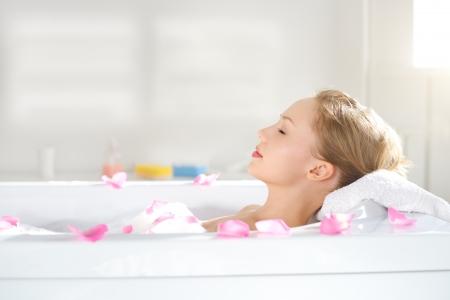 descansando: Una muchacha atractiva se relaja en ba�o sobre fondo claro Foto de archivo