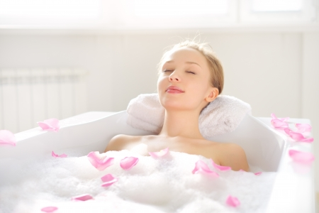 young girl bath: An Attractive girl relaxing in bath on light background Stock Photo