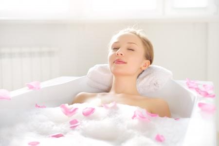 Una ragazza attraente che si distende nel bagno su priorità bassa chiara Archivio Fotografico - 17823459