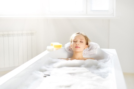lying in bathtub: An Attractive girl relaxing in bath on light background Stock Photo