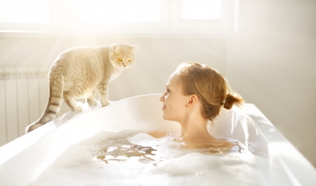 An Attractive girl relaxing in bath on light background Foto de archivo