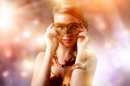 Beautiful girl in carnival mask on dark background photo