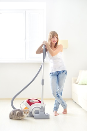 Attractive girl with vacuum cleaner photo