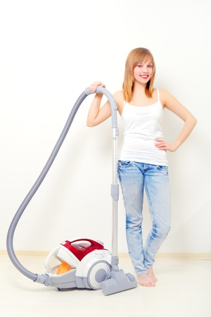 dusting: Attractive girl with vacuum cleaner on light background
