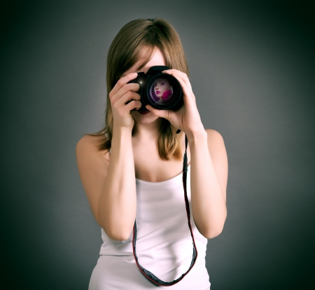 girl with digital camera on gray background photo