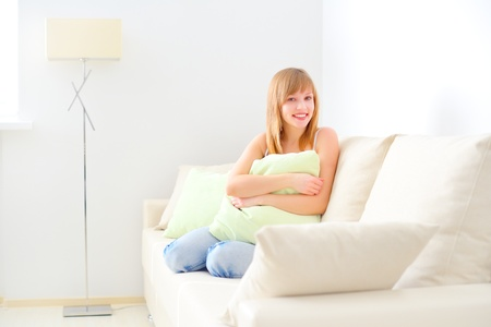smiling girl sitting on sofa  light room Stock Photo - 18521393