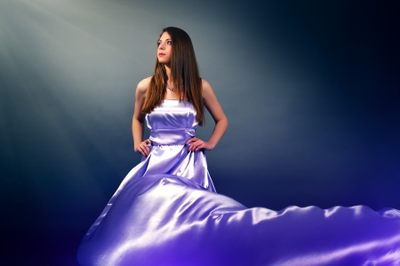 Beautiful girl in violet long dress on black background photo