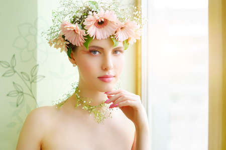 faceart: beautiful girl wearing wreath of flowers on light background Stock Photo
