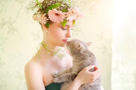 beautiful girl wearing wreath of flowers on light background photo