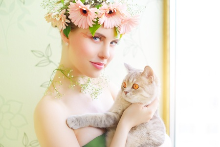 british people: beautiful girl with cat on a light background