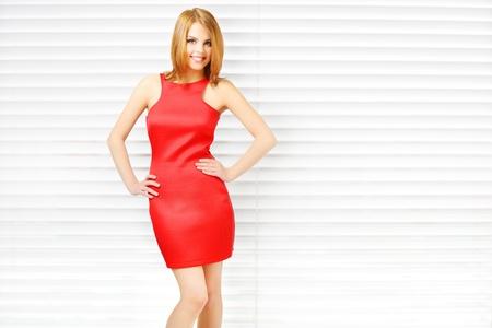 美しいメイク明るい背景で赤いドレスの官能的な女の子