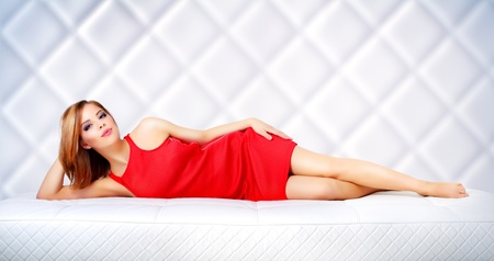 Elegant girl lying on the couch on light background photo
