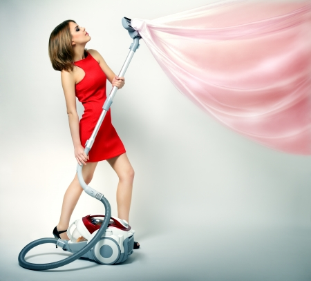vacuum: Sexy girl using vacuum cleaner. light background