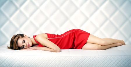 Sleeping girl on a leather sofa. light background