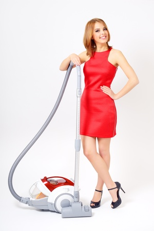 vacuuming: Attractive girl with vacuum cleaner on light background