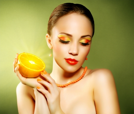 Girl with beautiful make-up holding orange fruit on green background Stock Photo - 19562164