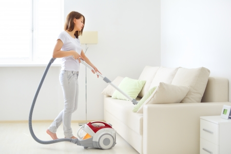 vacuum cleaning: Attractive girl with vacuum cleaner on light background