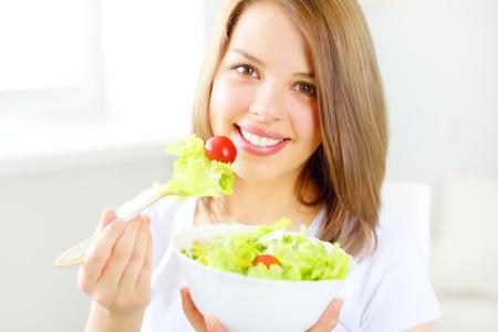 Teenager girl eating salad on light background photo