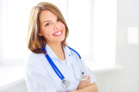 Portrait of a happy female doctor on light background photo