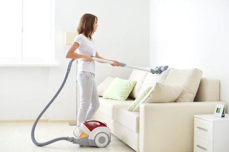 Attractive girl with vacuum cleaner on light background photo