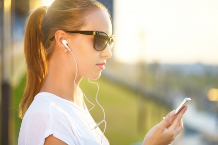 Teenage girl listening to music. background of the street Foto de archivo