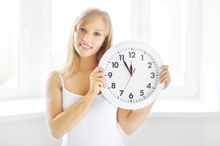 smiling girl with wall clock on light background