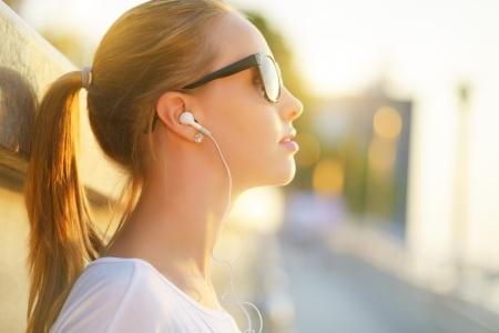 Teenage girl listening to music  background of the street Foto de archivo