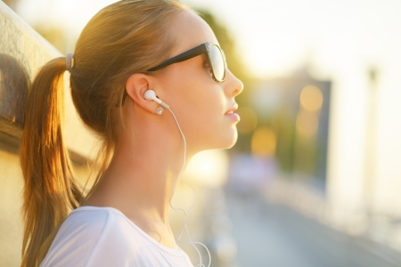 Teenage girl listening to music  background of the street Stock Photo