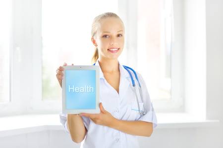 Female doctor with tablet pc on light background photo