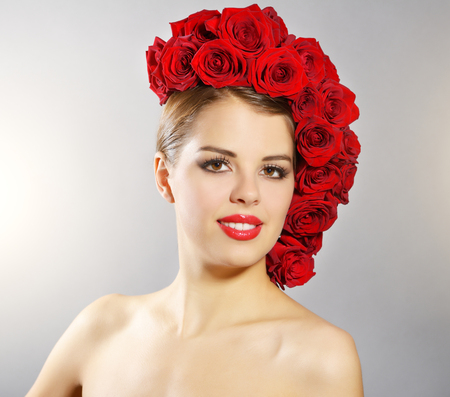 Portrait of smiling girl with red roses hairstyle. light background photo