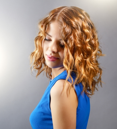 Pretty girl with short curly hair on light background photo